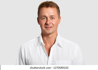 Portrait of handsome blue eyed man with confident expression, wears white shirt, looks at camera, being prosperous businessman, poses indoor. Masculinity concept. Attractive elegant male teacher