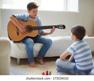 Portrait of handsome boy playing the guitar with his brother near by