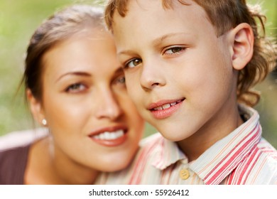 Portrait of handsome boy smiling at camera with his mother on background