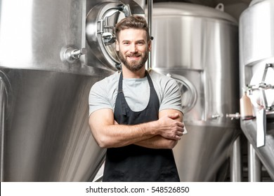 A portrait of handsome brewer in uniform at the beer manufacture with metal containers on the background
