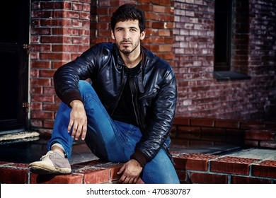 Portrait of a handsome brunet man in black leather jacket standing by a brick wall.
