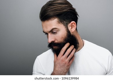 Portrait of handsome brutal masculine young bearded male looking down, touching his beard. posing on a gray studio background. Portrait of young European fashion barber with trendy beard.