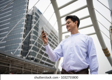 Portrait of Handsome Burmese or Myanmar businessman with longyi traditional dress using smart or mobile phone in Bangkok Modern city. Fintech Foreign Business man using 4g data technology.