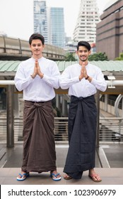 Portrait of Handsome Burmese or Myanmar men with longyi traditional dress perform salute or pay respect hand sign in Modern city. Smart guys smiling in traditional suit. Traditional welcoming gesture.