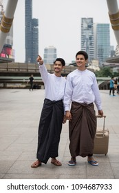 Portrait of Handsome Burmese or Myanmar men with longyi traditional dress with luggage in Modern Bangkok city. Smart guys smiling in traditional suit. Work and travel in Foreign country