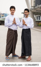 Portrait of Handsome Burmese or Myanmar men with longyi traditional dress perform salute or hello hand sign in Modern city. Smart guys smiling in traditional suit. Traditional welcome gesture.