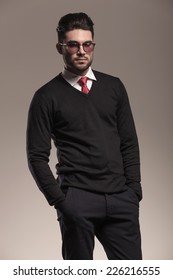 Portrait of a handsome business man holding his hands in pocket while looking at the camera. On grey background.