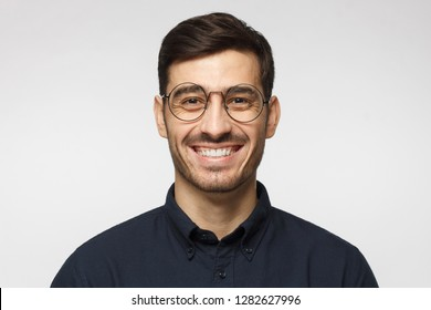 Portrait of handsome business man laughing, isolated on gray background