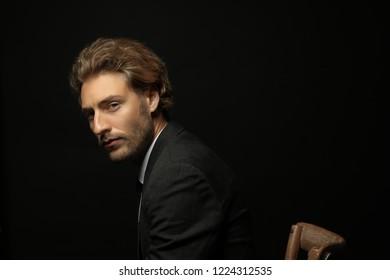 Portrait of handsome businessman against black background