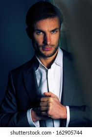 Portrait of a handsome businessman in a business suit on a dark background