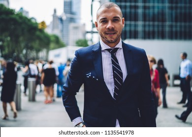 Portrait of handsome businessman dressed in formal wear looking at camera spending free time in modern city.Successful entrepreneur in expensive elegant suit standing on street of downtown