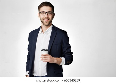 Portrait of a handsome businessman in eyeglasses with a cup of coffee.