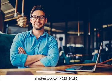 Portrait of handsome businessman in eyeglasses satisfied with achievements in economics working to reach high targets, young proud CEO feeling confidence in himself and creative startup project