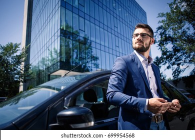 Portrait of a handsome businessman in glasses standing near the car outdoors in front of the modern building facade