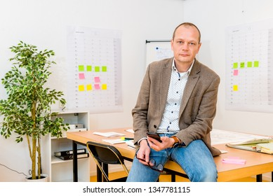 Portrait of handsome businessman holding smartphone while sitting on conference table at office