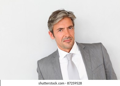 Portrait of handsome businessman standing on grey background