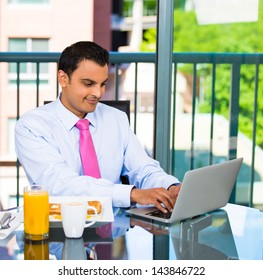 Portrait of handsome businessman or student eating breakfast and happily typing and working on his laptop, isolated on city background with trees