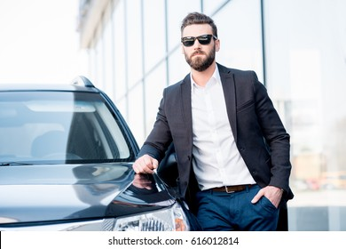 Portrait of a handsome businessman in sunglasses standing near the car outdoors in front of the modern building facade