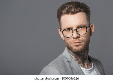 portrait of handsome businessman in trendy eyeglasses, isolated on grey