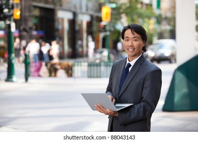 Portrait of handsome businessman using laptop and smiling