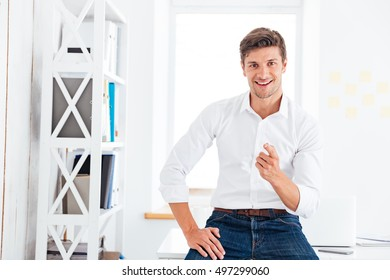 Portrait of a handsome businessman in white shirt pointing finger at camera while sitting on the table at office