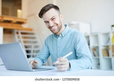 Portrait of handsome businessman working in office and smiling happily at camera, copy space