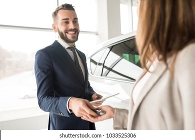 Portrait of handsome car salesman giving car keys to young woman standing next to white shiny luxury car in dealership showroom