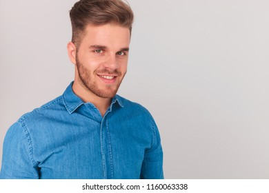 portrait of handsome casual man smiling while standing on light grey background