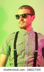 Portrait of handsome casual stylish young man with sunglasses, plaid short sleeve shirt and braces in green and red colored lights