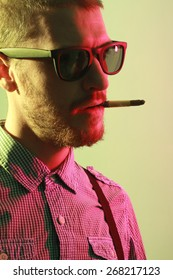 Portrait of handsome casual stylish young man with sunglasses, plaid short sleeve shirt and braces smoking cigarette with holder in green and red colored lights