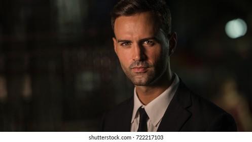 Portrait of a handsome caucasian business man in dark alley