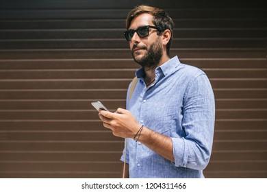 Portrait of handsome Caucasian businessman holding smartphone.
