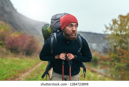 Portrait of handsome Caucasian hiker young male hiking in mountains with travel backpack. Traveler man with beard relaxing after trekking during vacation. Travel, people, healthy lifestyle concept