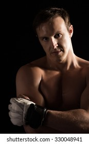 Portrait of a handsome caucasian male mixed martial arts fighter. The guy is wearing white mma gloves.