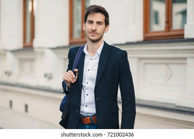 Portrait of handsome caucasian man with backpack holding the strap with hand looking to right, on the street. Young businessman walking outdoors in town. Urban lifestyle concept.