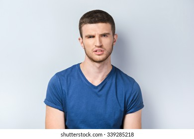 Portrait of handsome caucasian man standing on grey background. Young man looking at camera