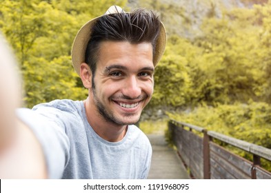 Portrait of handsome caucasian man taking a selfie on vacation on a nature background