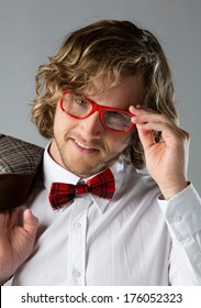 Portrait of a handsome caucasian man wearing a white buttoned shirt, red checkered bow tie and funky glasses. The man is posing and holding a brown jacket.