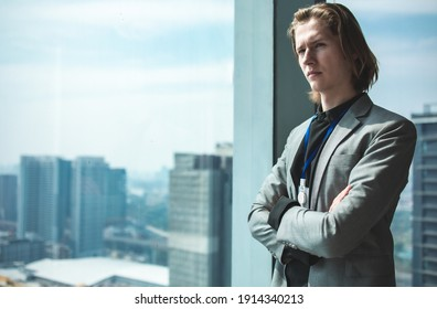 Portrait of a handsome CEO smiling.businessman in suit standing in office with hands on waist, CEO looking through window. Horizontal photo banner for website header design with copy space for text