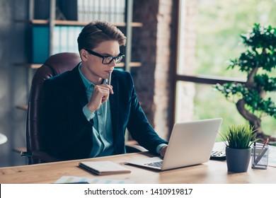 Portrait of handsome charming entrepreneur sit table desk top use user pc modern technology have data presentation research wear black jacket suit touch chin pen industrial studio loft