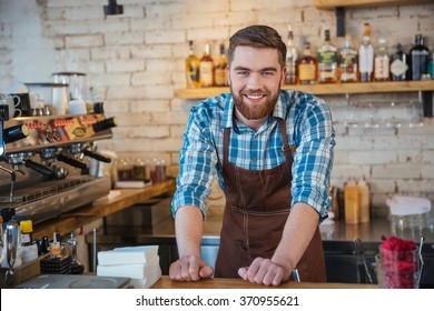 Portrait of handsome cheerful barista smiling and standing in coffee shop