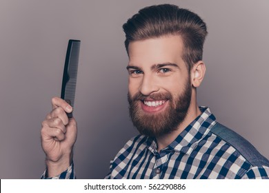 Portrait of handsome cheerful bearded man showing comb