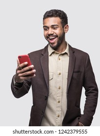 Portrait of handsome cheerful smiling young man using smartphone. Surprised laughing joyful men with mobile phone studio shot. Isolated on gray background