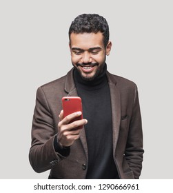 Portrait of handsome cheerful smiling young man using smartphone isolated on gray background. Laughing joyful men with mobile phone studio shot.