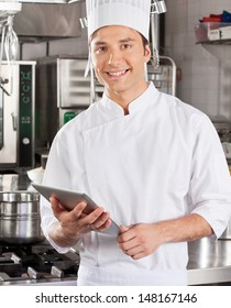 Portrait of handsome chef with tablet computer in commercial kitchen