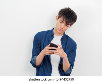 Portrait of a handsome Chinese young man in blue shirt looking at her mobile phone, serious or worried expression, isolated on white background.