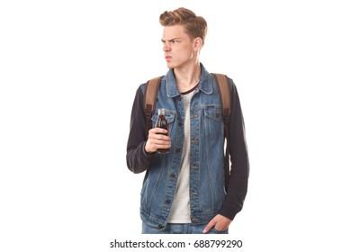 Portrait of handsome college boy holding glass bottle of cola