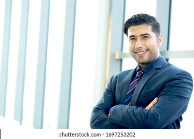 Portrait Handsome confident businessman wearing suit standing Successful businessman with folded arms  standing over office background. caucasian looking at camera. joyful smile with copy space.