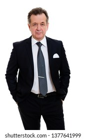Portrait of handsome confident caucasian mature businessman 55-60 years old in black suit standing with his hands in pockets in front on isolated white background.