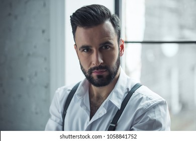 Portrait of handsome confident man looking at camera, window in the background